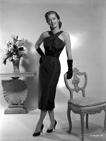 Vera Miles posed standing in a black, ankle length, halter dress and gloves, while leaning onto a c