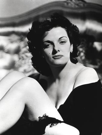 Jane Russell Seated on the Bed in Black Silk Robe with Knees Bent and Arms Crossed Around the Legs