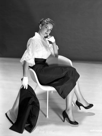 Vera Miles casually posed sitting in a white chair, wearing white chiffon top