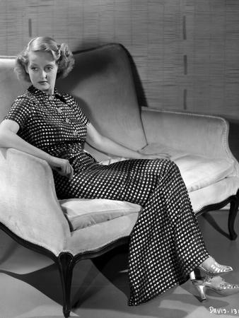 Bette Davis Seated on a White Couch