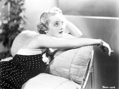 Bette Davis sitting on the Couch while Smoking a Cigarette in Black Sleeveless Polka Dot Dress