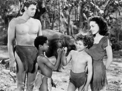 Johnny Weissmuller standing with Two Kids and a Woman in a Movie Scene