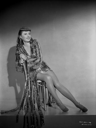 Barbara Stanwyck sitting on Chair in Black and White Portrait