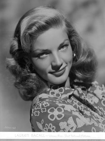 Lauren Bacall smiling in Floral Dress in Black and White Portrait