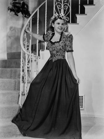 Judy Garland in an amazing dress at the bottom of spiral stair case