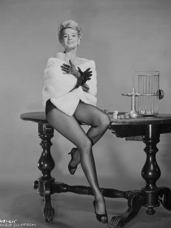Angie Dickinson sitting on Table in Sexy Outfit with White Coat