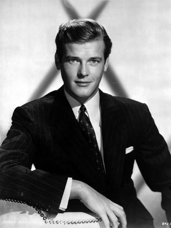 Roger Moore Posed in Black Suit With White Background