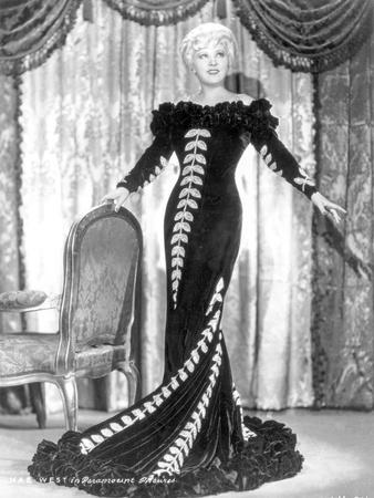 Mae West standing in Black Long Gown with Arm's Open