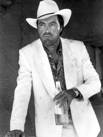 Powers Boothe Posed in White Suit With Bottle