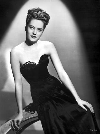 Alexis Smith sitting and wearing a Black Dress