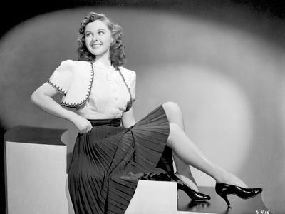 Susan Hayward sitting in Black Skirt and Shoes