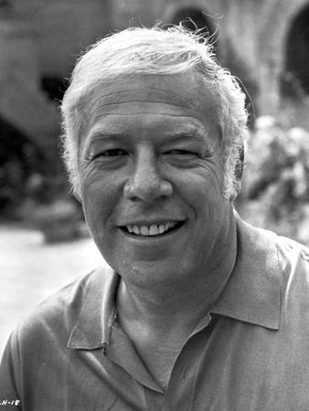 George Kennedy smiling in White polo shirt