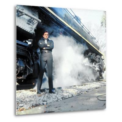 Country Music Star Johnny Cash Wearing Black Clothing and Standing in Front of a Locomotive