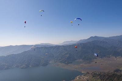 Dozens of Paragliders Enjoy Amazing Views of the Himalayas Above Phewa Lake, Nepal, Asia