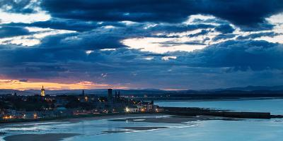 Looking across Bay to St. Andrews Harbour and Pier with Sun Setting Beyond City as Dusk Falls