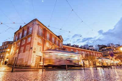 City Lights on the Typical Architecture and Old Streets at Dusk While the Tram 28 Proceeds, Alfama