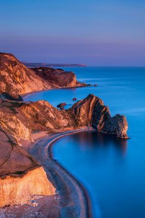 The Limestone Arch of Durdle Door and St. Oswald's Bay Extending Along the Jurassic Coast at Dusk