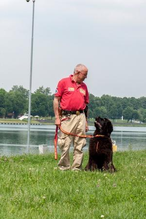 A Newfoundland Dog Trained for Rescue at Sea, with an Instructor at a Lake Near Milan