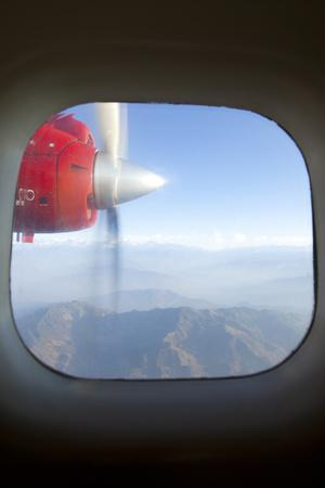 View of the Himalayan Mountains and Moving Airplane Propeller Seen Through Window