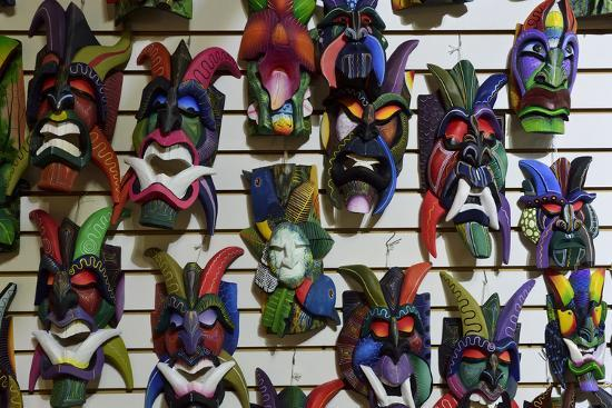 Colorful Carved Wooden Masks Hang For Sale On A Wall In A Tourist Shop In Costa Rica