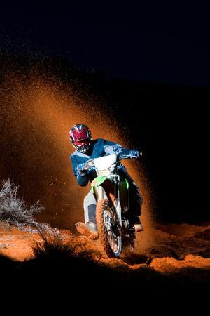 A Motorcyclist Rides on Sand Dunes, Kicking Up Sand Behind Him