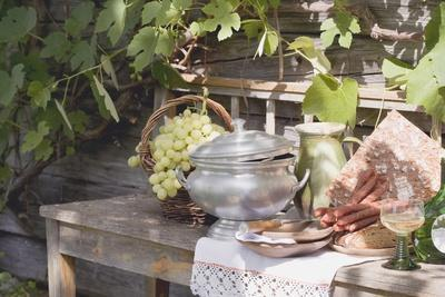 Still Life with Grapes, Bread, Sausages and Wine in Front of Farmhouse