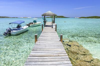 A Wood Pier Leads to Moored Boats and Clear Tropical Waters Near Staniel Cay, Exuma, Bahamas