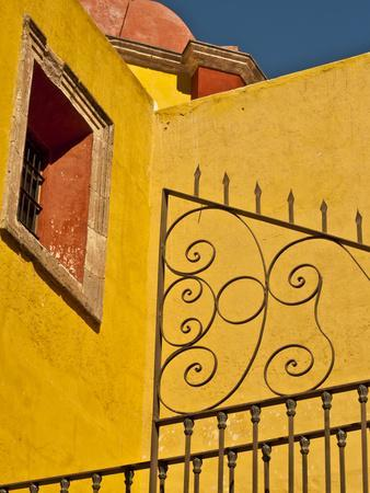 Wrought Iron Fence Against a Yellow Church Wall with Barred Window Against a Blue Sky, Mexico