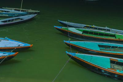 India, Varanasi 9 Blue, Red and Green Rowboats on the Green Water of the Ganges River