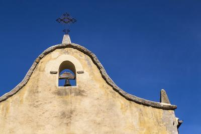 Italy, Sardinia, Gavoi. the Bell and Cross of an Old Church, Backed by a Blue Sky