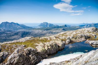 A Small Lake with Snow and View towards Mountains and the Sea in Northern Norway