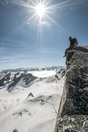 A Young Male Climber on the Summit of Pigeon Spire, Bugaboos, British Columbia