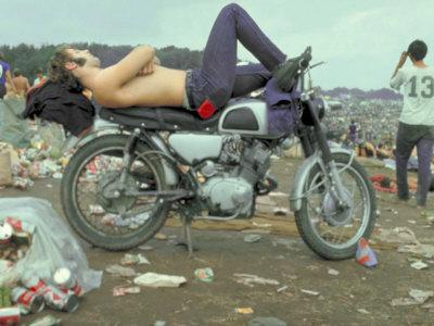 Shirtless Man in Levi Strauss Jeans Lying on Motorcycle Seat at Woodstock Music Festival