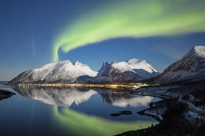 Northern lights and stars light up the snowy peaks reflected in sea, Bergsbotn, Senja, Norway