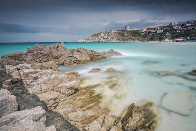 Storm clouds frame the village overlooking the turquoise sea, Santa Teresa di Gallura, Italy