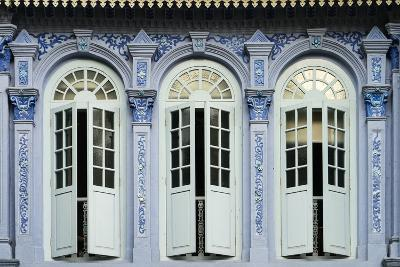 Traditional shophouse windows open out onto a street in the Orchard Road neighborhood in Singapore