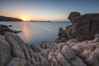 White cliffs and blue sea framed by the lights of sunset Santa Teresa di Gallura, Sardinia, Italy