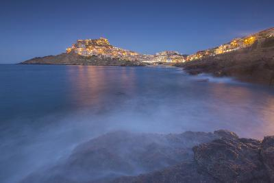 Waves frame the village perched on promontory at dusk, Castelsardo, Gulf of Asinara, Italy