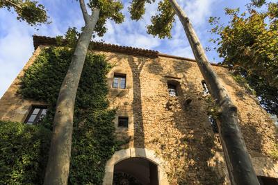 Gala Dali Castle Museum facade amidst tall trees, medieval home of Salvador Dali, Pubol, Baix Empor