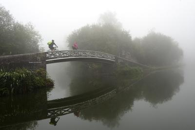 A cyclist on a bridge on Birmingham Canal Navigations (BCN), Birmingham, West Midlands, England, Un