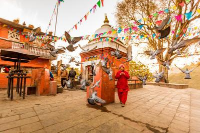 Woman walking and praying with pigeons at the hilltop temple, Bhaktapur, Kathmandu Valley, Nepal, A
