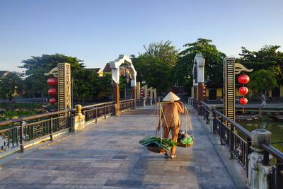 A woman carrying baskets on a yoke over the Lantern Bridge in Hoi An, Quang Nam, Vietnam, Indochina