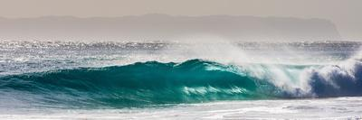 Panorama of a beautiful backlit wave breaking off a beach, Hawaii