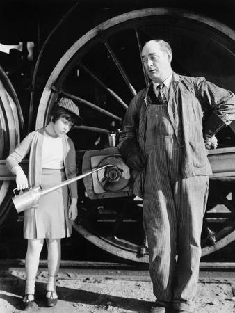 Little Girl with an Oil Can Standing Next to a Locomotive and the Engine Driver