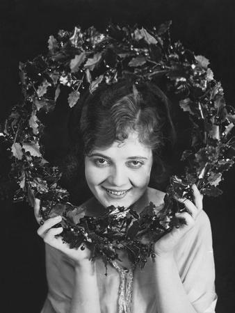 Portrait of Woman Holding Christmas Wreath