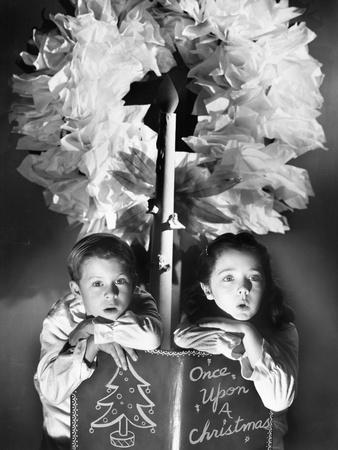 Two Children Sitting under a Wreath Holding a Christmas Story Book