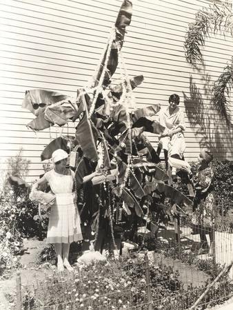 Three Women Decorating Banana Tree for Christmas