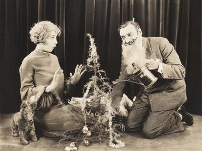 Woman Watching Man in Fake Beard Watering Christmas Tree