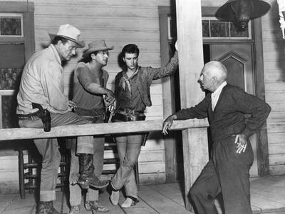 RIO BRAVO, 1959 directed by HOWARD HAWKS On the set, John Wayne, Dean Martin and Ricky Nelson with