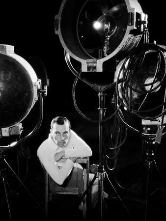 American silent screen comedian and actor Buster Keaton (1895 - 1966) surrounded by studio lighting